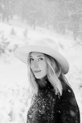 Old Pine production manager Susan stands in a snowy mountain scene, looking at the camera wearing a white Stetson hat and black turtleneck sweater.