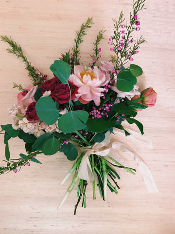 A blush, pink, and coral bouquet featuring trailing silk ribbons