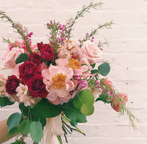 a lush bouquet featuring peonies, eucalyptus, and blush and coral blooms