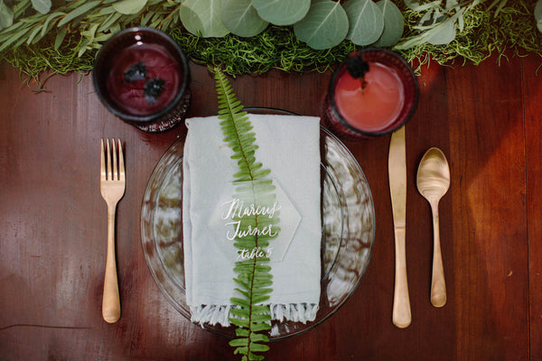 A wedding place setting with fern and lucite place cards