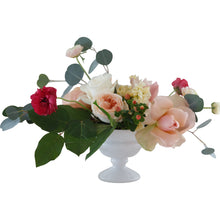 A peach and blush garden-style arrangement in a white footed bowl, suitable for a wedding centerpiece