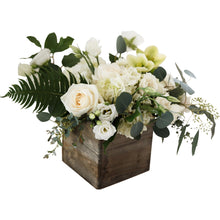 A lush, white and green centerpiece in a wooden box
