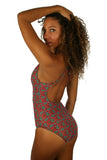 Side view of crisscross strap tank swimsuit in green Hibiscus print.