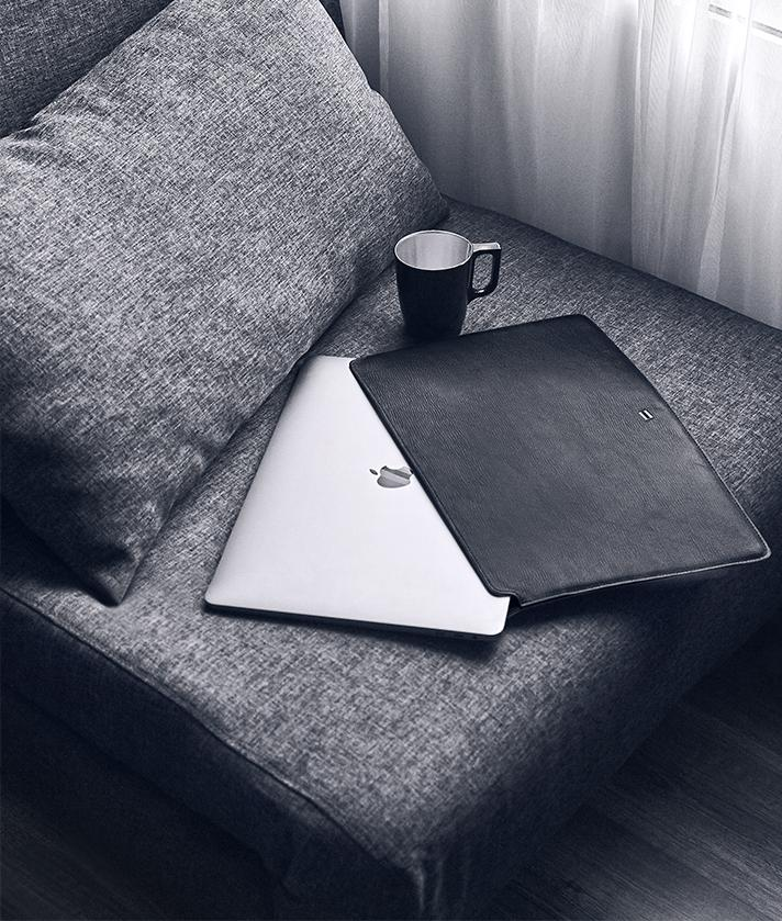 macbook with suritt leather sleeve in a sofa