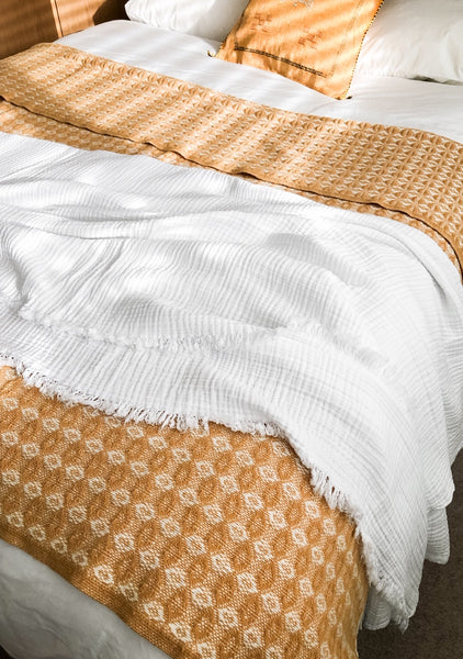 mustard wool blanket and white textured cotton throw from sand and salt, covering a bed.