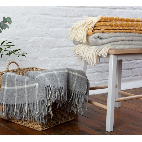 Lifestyle picture of grey check wool throw in a basket, with a mustard wool throw and light grey wool throw folder on a wooden stool beside the basket.