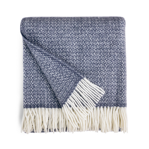 Picture of a folded Welsh wool throw in Slate Blue which is a medium shade of greyish blue. Off white tassels at both ends.