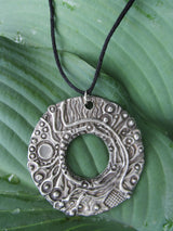 "Abstract, textural circular pendant.  Caste in pewter.  Adjustable leather necklace to 26""."