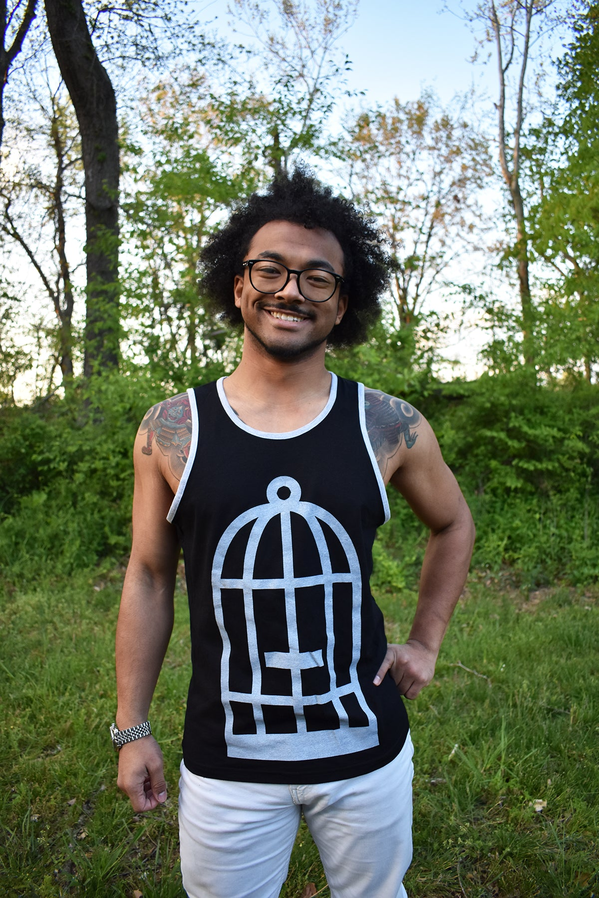 Male model wearing a black and grey ringer tank top with the No Egret's birdcage logo in grey on the front.