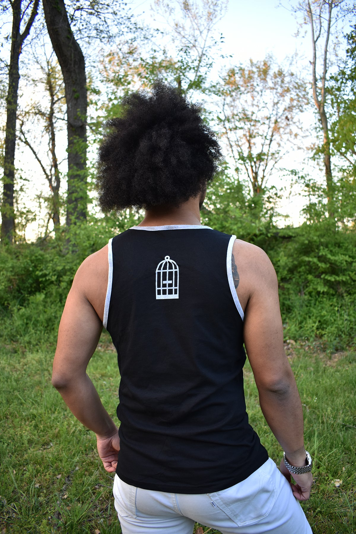 Male model wearing a black and grey ringer tank top with a small No Egret's birdcage logo in grey on the back between the shoulders.