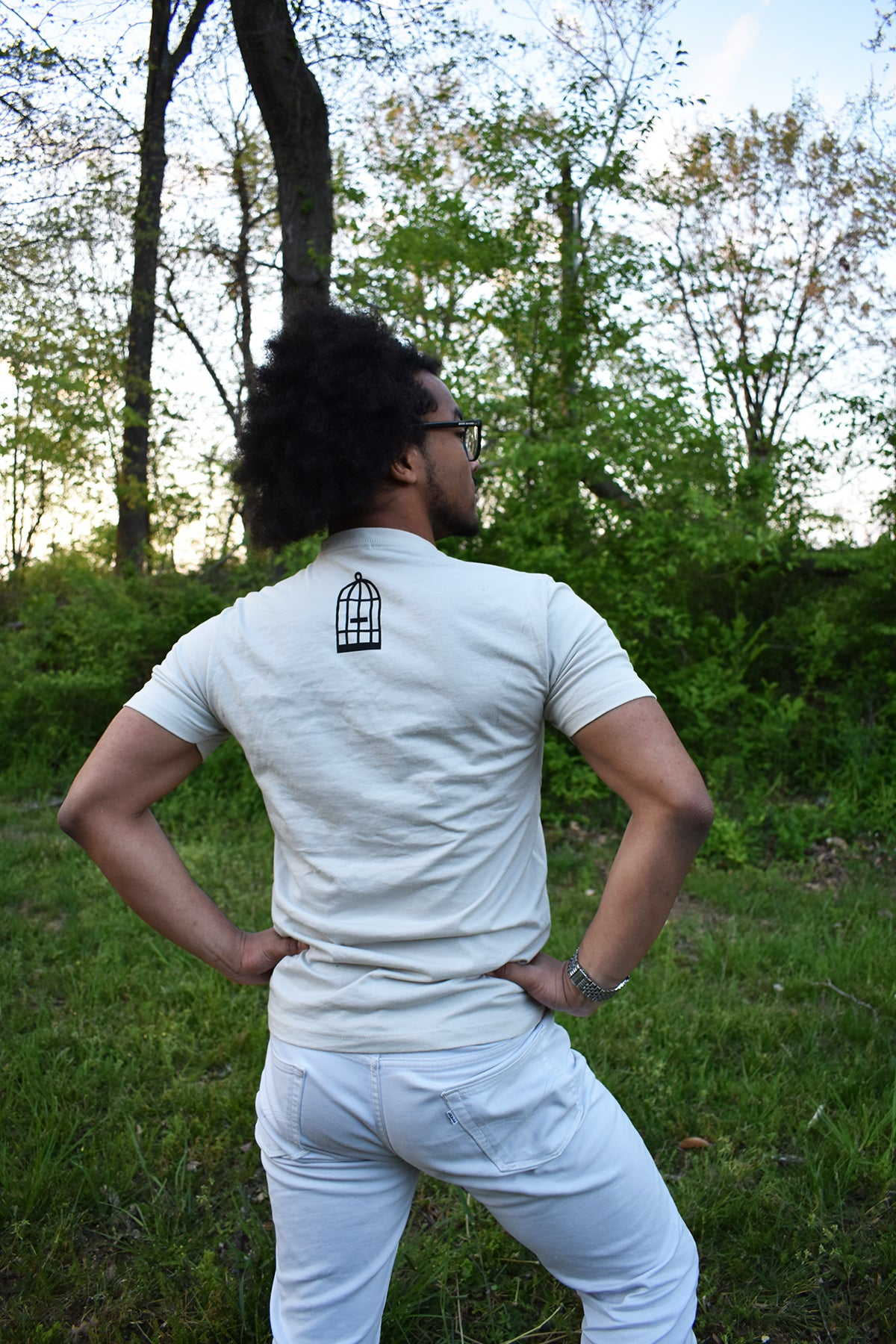 Male model wearing a cream colored t-shirt with a small, No Egrets birdcage logo in black on the back between the shoulders.