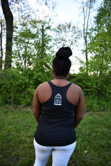 Female model wearing a dark grey racerback tank top a small No Egrets Birdcage logo in light grey on the back between the shoulders.