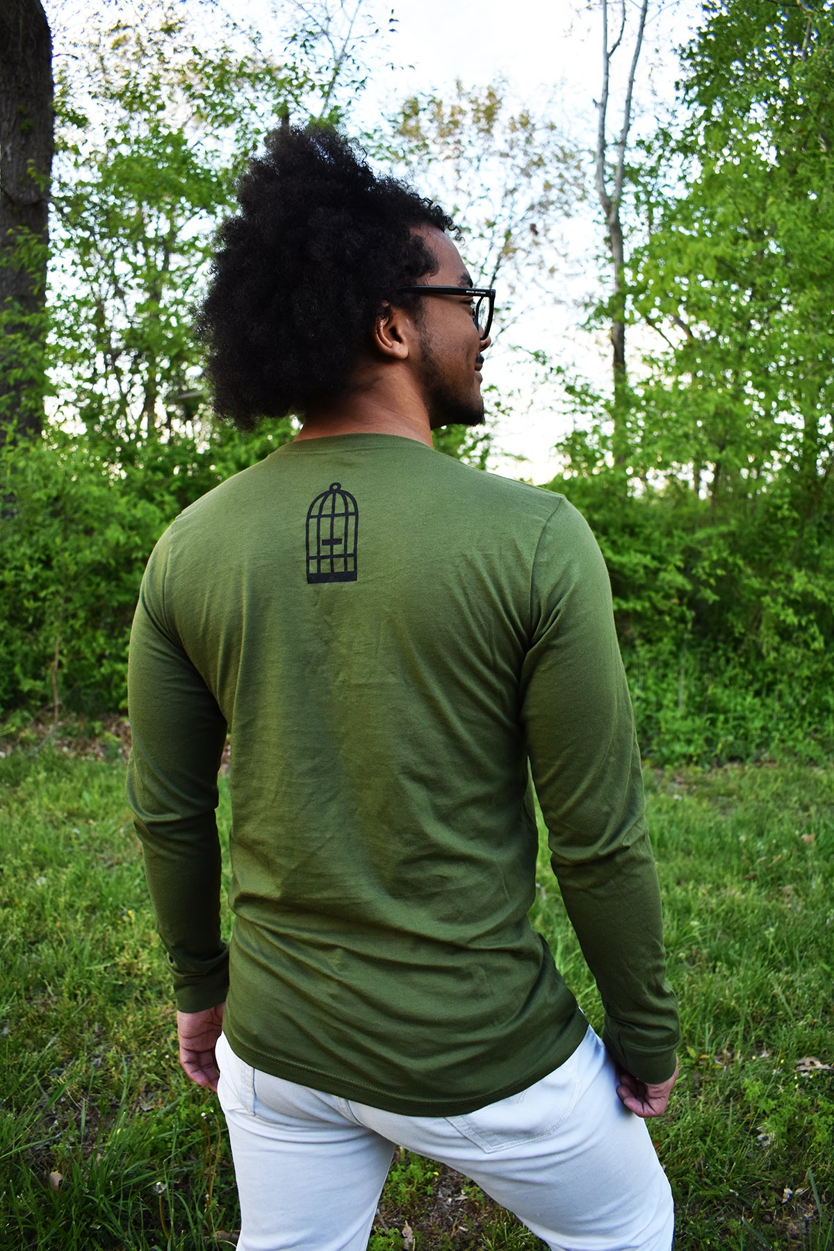 Male model wearing a green, long-sleeved shirt with a small, No Egrets Birdcage logo in black on the back in between the shoulders.