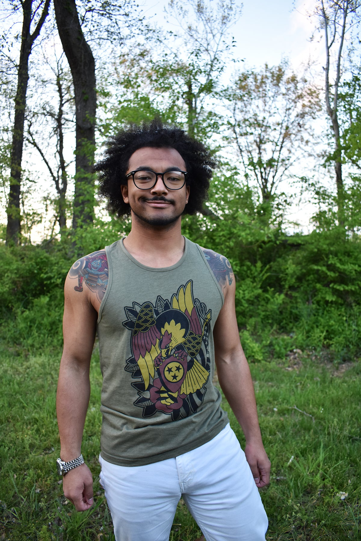 Male model wearing a green tank top with Brice Hamm's Tri-Star Eagle design in black, gold, and red on the front.