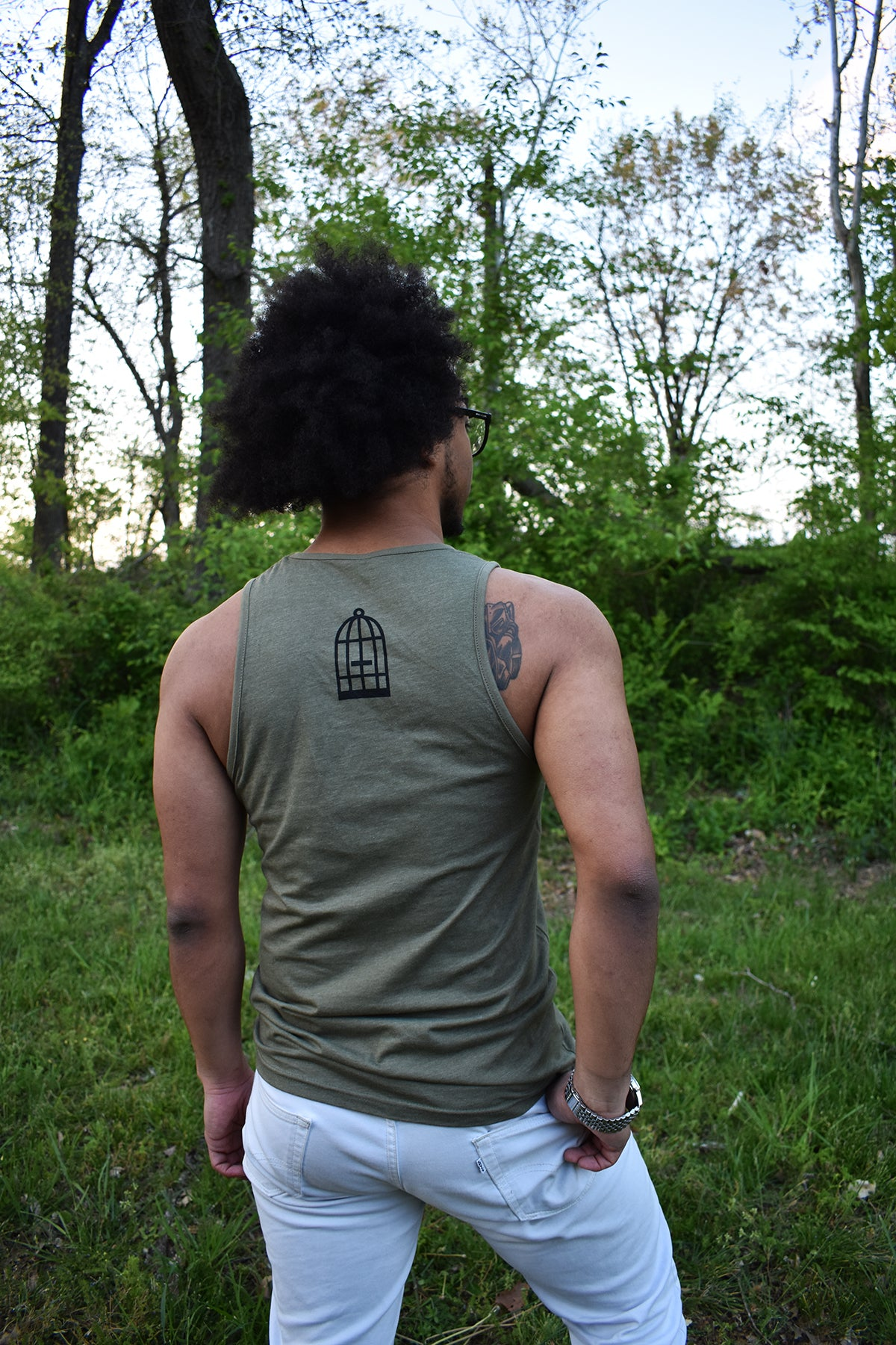 Male model wearing a green tank top a small No Egrets Birdcage logo in black on the back between the shoulders.