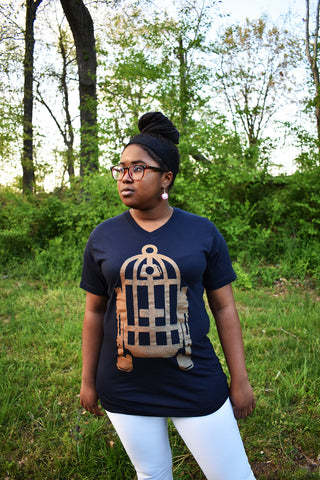 Female model wearing v-neck navy t-shirt with Fred Palmer's Robot Birdcage design in gold on the front.