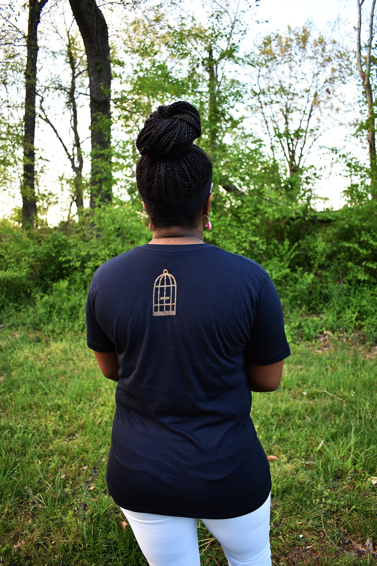 Female model wearing v-neck navy t-shirt with a small, No Egrets Birdcage logo in gold on the back between the shoulders.