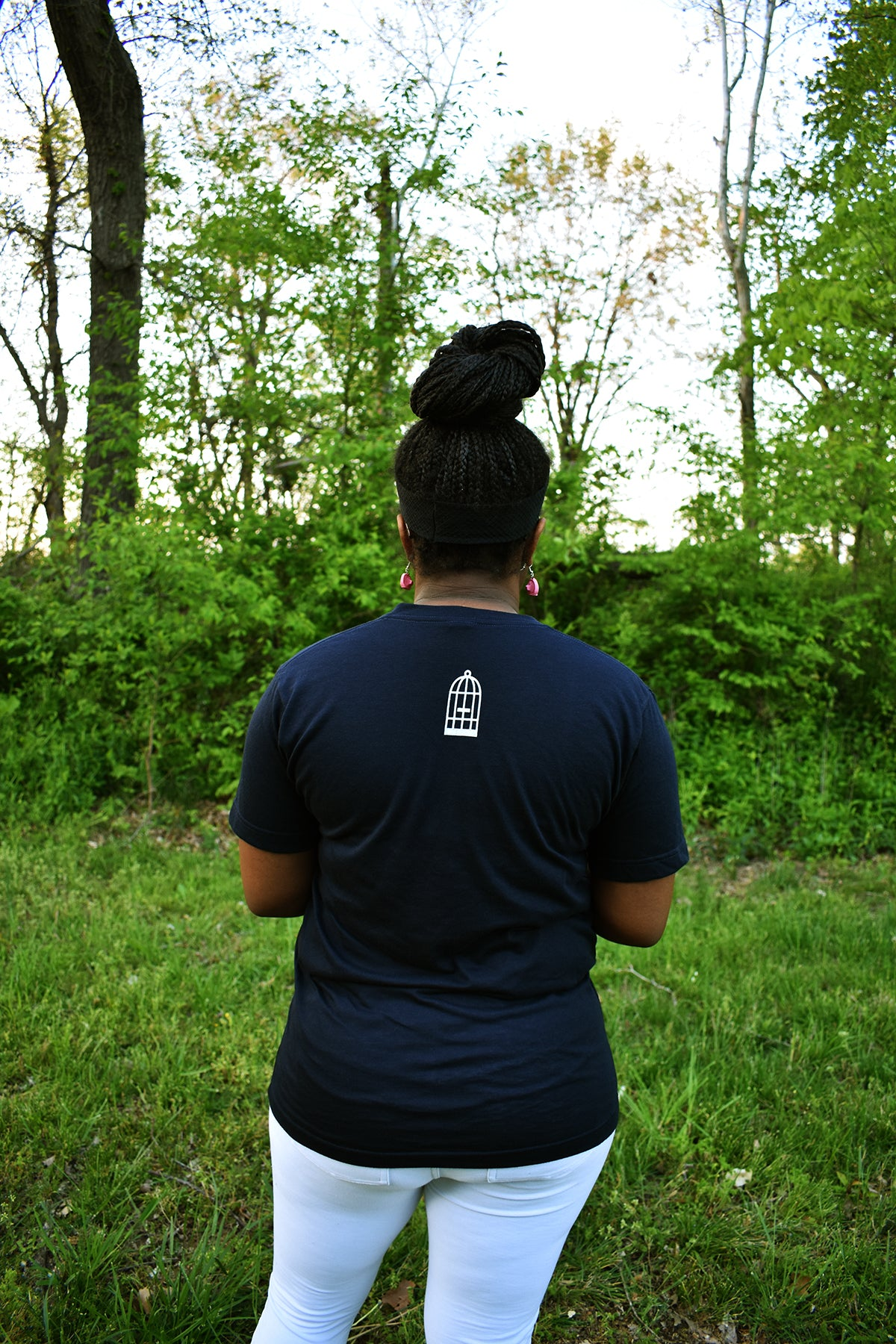 Female model wearing v-neck navy t-shirt with a small, No Egrets Birdcage logo in white on the back between the shoulders.