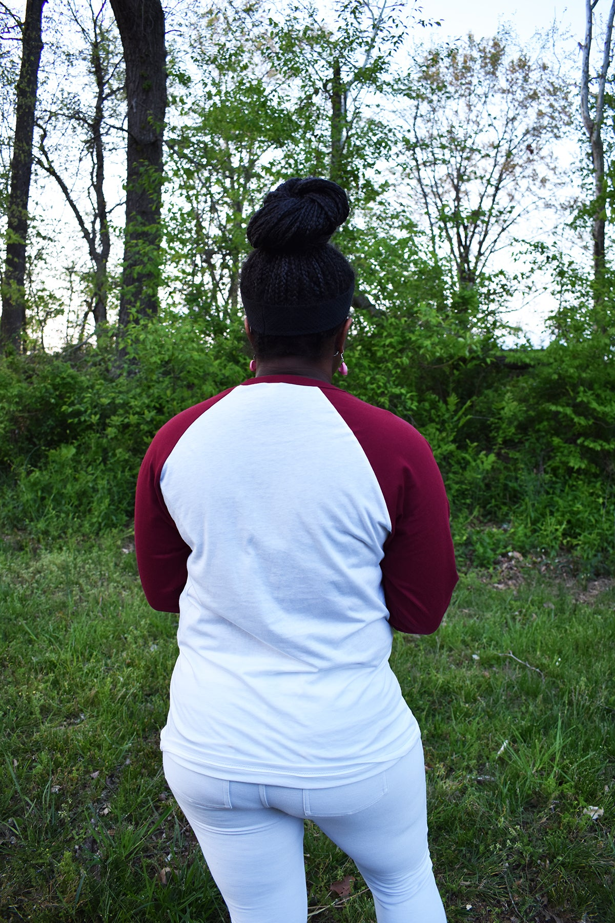Female model wearing a baseball tee with a white body and red sleeves.