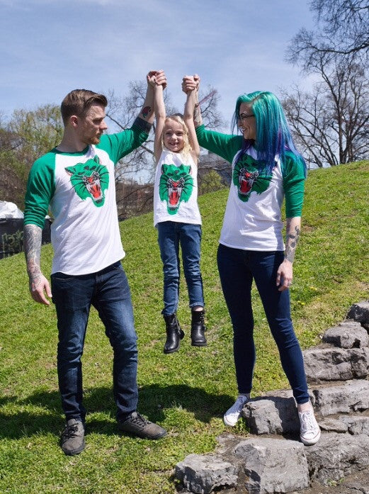 Three models (adult male, adult female, and female child) all wearing a baseball tee with a white body and green sleeves with Ben Drawdy's Battle Cat design in green, red, and black on the front.