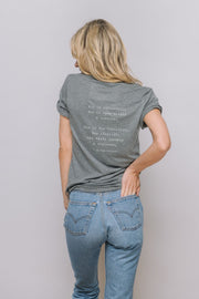 "grey tee with ""She is optimistic. She is open minded & curious. She is the traveller, the idealist, the truth speaker & explorer"" on it"
