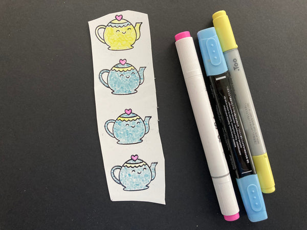 colored stamped teapots. on white shrink plastic