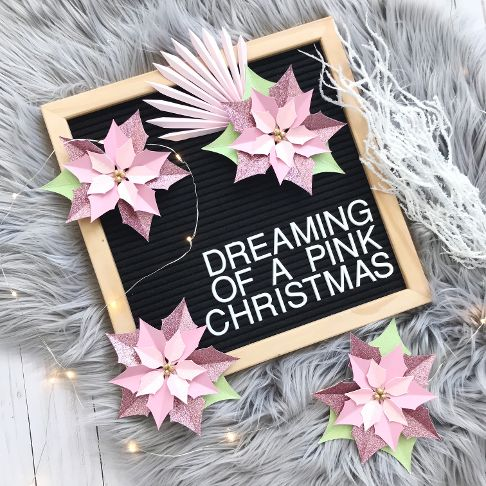 glitter paper poinsettias on a black letterboard sign