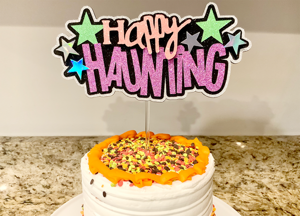 halloween cake topper made with glitter paper on an orange and white cake
