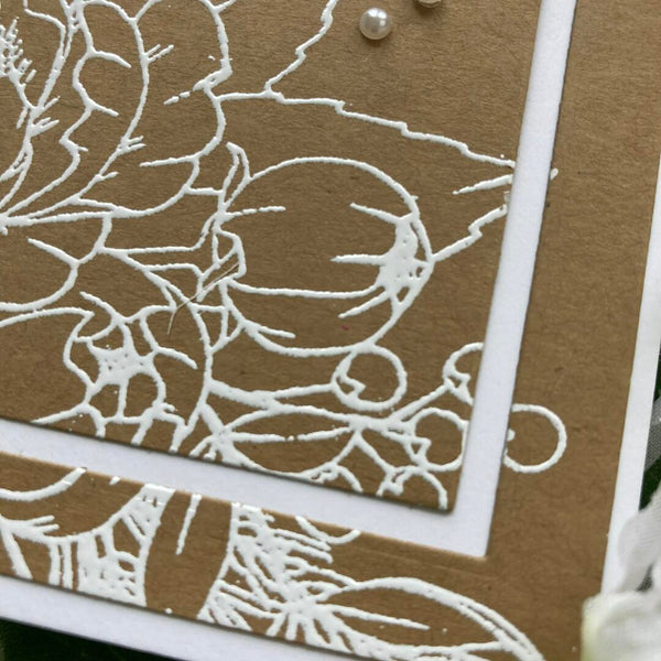 close up of white embossing on kraft cardstock