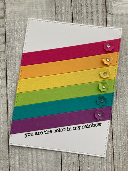 rainbow cardstock strips on a white background with flowers