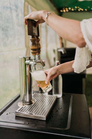 Woman pours cider from a keg