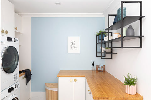 Laundry with white cabinets with brass furniture knobs. Open wall shelf with black inserts on right side