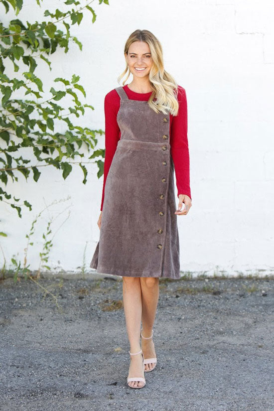 a woman in a corduroy jumper dress