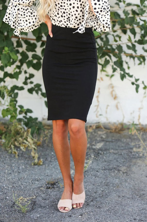 a woman wearing a simple black pencil skirt