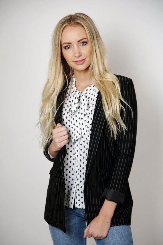 a woman wearing a polka dot blouse beneath a pinstripe blazer