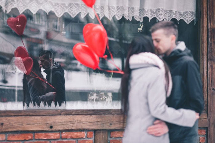 a couple with heart-shaped balloons sharing a kiss