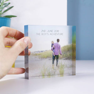 A square clear acrylic block with a photo printed onto the block, with a hand on one side of the block to give an idea of scale, this is 10cm x10cm big and is freestanding. Acrylic block with personalised text on and an image of dad holding son on the beach.