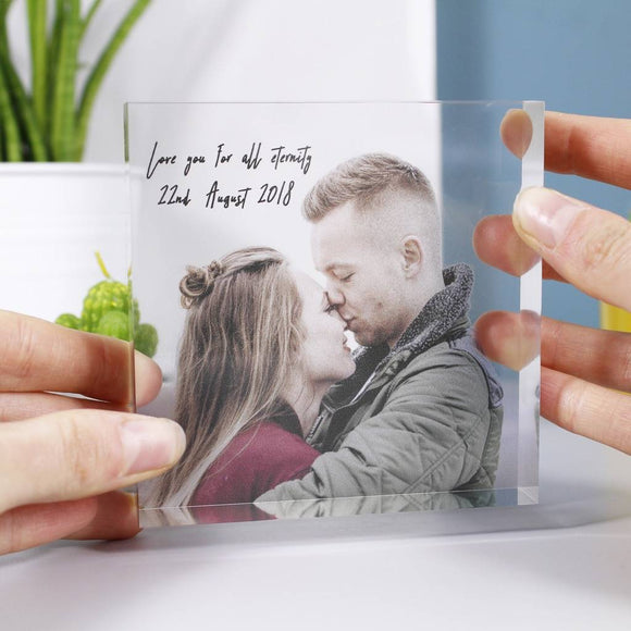 Clear Acrylic block being held with two hands to show the scale of the block. Has a photo of couple and text in a script font which can be personalised