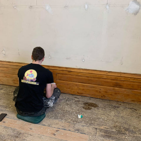 Josh oiling the skirting board after it being stripped of paint and sanded.