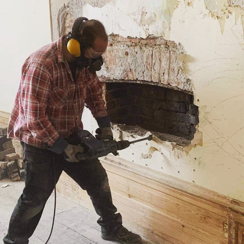 Matt chipping away to uncover the fireplace in the principal function room.