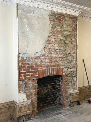 The principal function room's fireplace after having been uncovered once again.