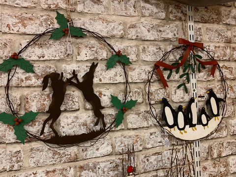 Metal penguin and hare Christmas wreaths at Happy Piranha Truro