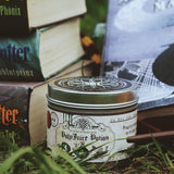 Happy Piranha's polyjuice potion candle in the grass with books.