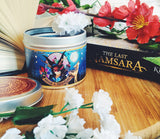 Iskari scented candle with lid off and the Last Namsara book.