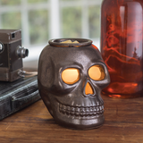 Skull shaped Illumination Wax Melt Warmer on a table switched on