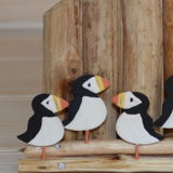 Puffins Sitting On A Coastal Groin Wood & Metal Ornament close up view | Happy Piranha
