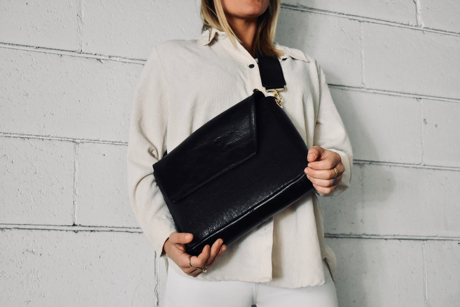 The Dena Roy Anna Crossbody bag combines two black leathers - a solid and a texturized crackle, paired with our Mable hand dyed liner. The Anna is the perfect versatile day to night bag. Featuring a shorter removable crossbody strap which hits a little higher on the body. If you're feeling it, remove the strap and use the body of the bag as a clutch.
