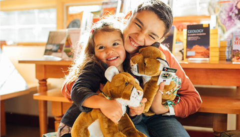 Brother and sister hug stuff animal lions with big smiles on their faces.