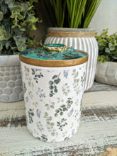 white and green floral candle with green teal gold agate lid