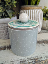 green and white polka dot candle canister with teal white sphere lid